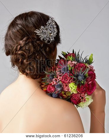 Bridal hairstyle with vintage style hair accessories and red rose bouquet. Brunette Bride. View from the back
