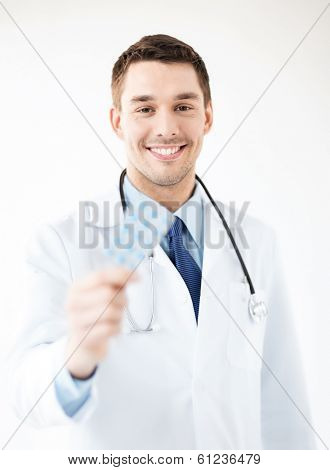 picture of young male doctor with pack of pills