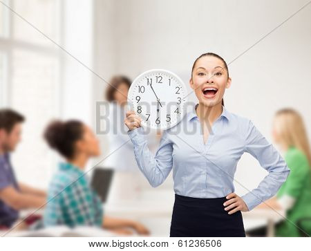 business, education and time concept - attractive teacher with wall clock