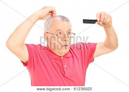 Surprised mature man holding a comb isolated on white background