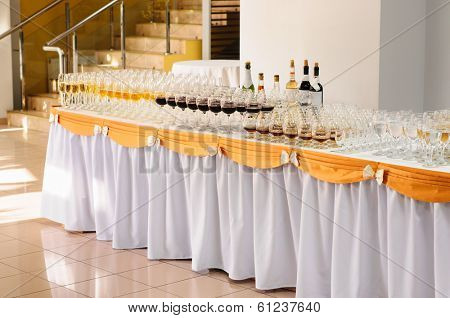 banquet table with alcohol drinks and rows of stemware