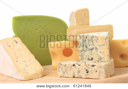Composition of cheese on wooden plate.