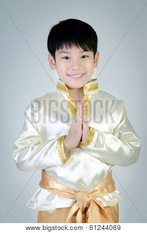Asian Cute Boy In Thai Costume Acting Hello In Thai On Gray Background .