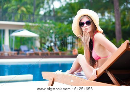 Happy young woman in bikini laying on chaise-longue air kiss