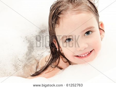 Smiling Little Girl Washing In Bath With Foam