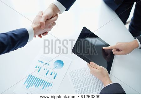 Managers shaking hands over business plans