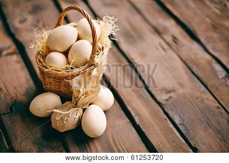 Image of wooden Easter eggs in the basket and near by, one of them wrapped in paper