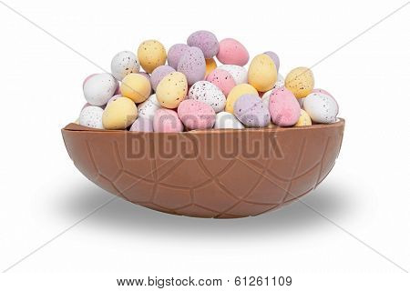 Half a chocolate Easter egg full of mini candy coated eggs, isolated on a white background.