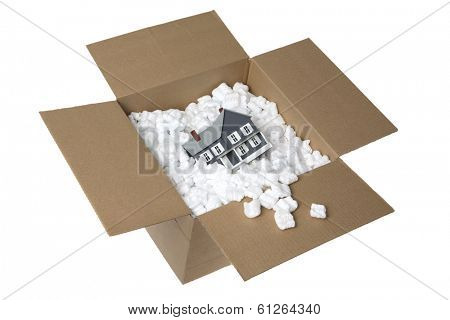 Cardboard box with plastic packaging and doll house on white background
