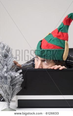 Man Hiding Behind Laptop With Elf Hat