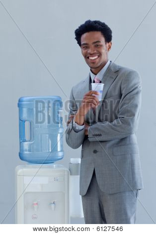 Businessman Drinking From A Water Cooler In Office