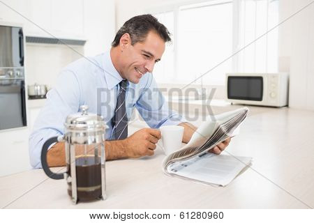 Smiling well dressed man with coffee cup reading newspaper in the kitchen at home