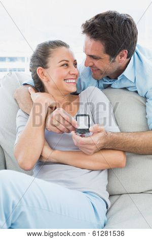 Happy woman being surprised by a marraige proposal at home in the living room