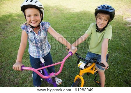 Portrait of smiling siblings riding bicycles at the park