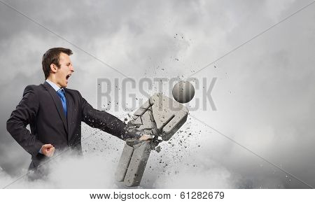 Angry young businessman fighting with stone opponent