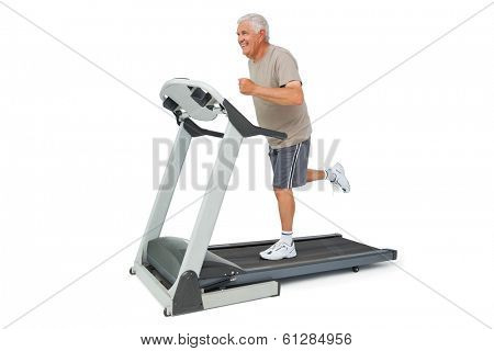 Full length of a senior man running on a treadmill over white background
