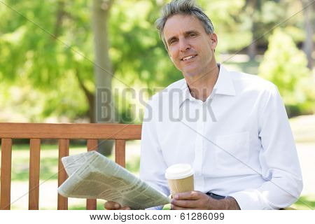 Portrait of confident businessman with disposable cup and newspaper in the park