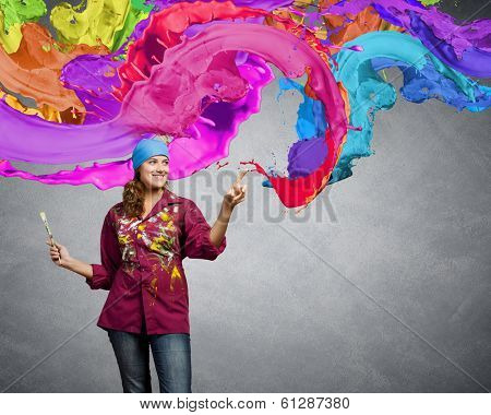 Young woman painter coloring wall with brush
