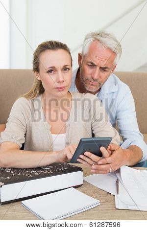Serious couple calculating their bills at the couch at home in the living room
