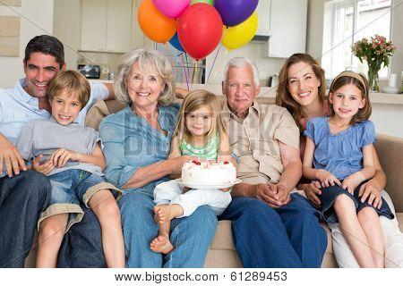 Portrait of multigeneration family celebrating girls birthday in living room