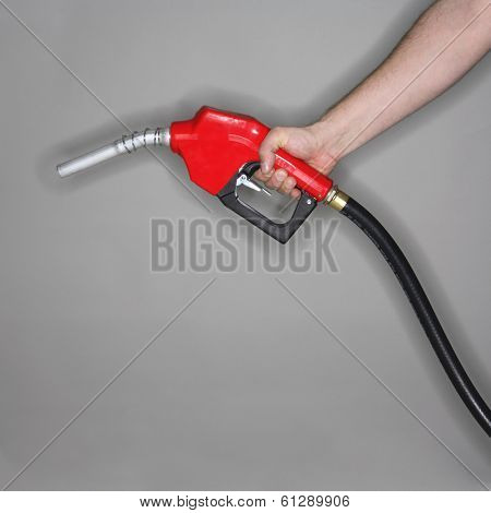 man holding gas hose with red nozzle on grey background