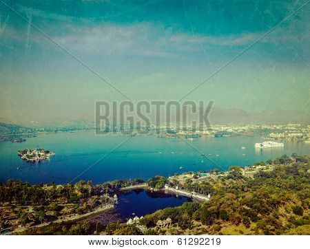 Vintage retro hipster style travel image of aerial view of Lake Pichola with Lake Palace (Jag Niwas) and Jag Mandir (Lake Garden Palace) with grunge texture overlaid.  Udaipur, Rajasthan, India