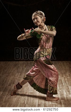 Vintage retro style image of young beautiful woman dancer exponent of Indian classical dance Bharatanatyam in Krishna pose
