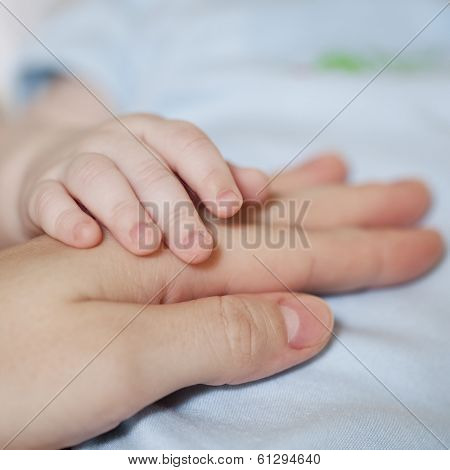 Mother holding tiny arms of newborn baby
