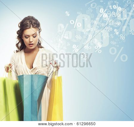 Young attractive shopper girl with shopping bags (discounts and sales concept).