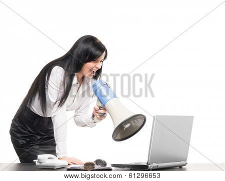 Angry and furious business woman screaming with megaphone at a computer, isolated on white.