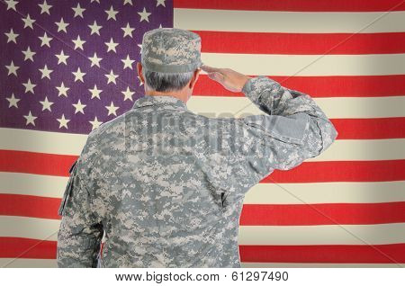 Closeup of a middle aged American soldier in fatigues saluting an old and weathered flag. The flag fills the frame and is out of focus. Man is seen from behind.