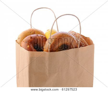 Closeup of a brown paper bag filled with a variety of different bagels. Bagels include: onion, blueberry, egg and multi-grain. Horizontal format isolated on white.