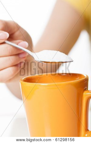 Woman Sweetening A Tea