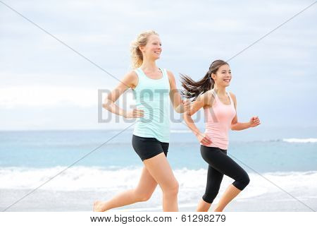 Runners - two women running outdoors training. Exercising female athletes jogging outside on beach smiling happy. Multiracial Asian and Caucasian woman in healthy lifestyle.