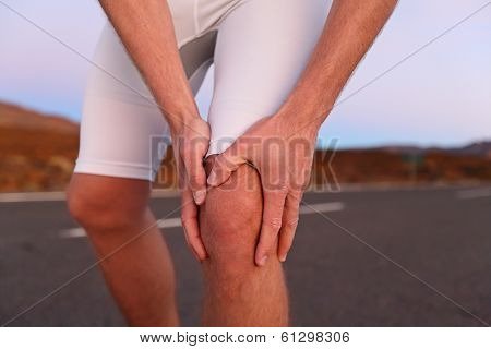 Knee pain - man with running sport injury. Male runner having knee problems during exercise outside.