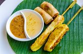 picture of por  - Vegetables spring roll and chicken satay on banana leaf - JPG
