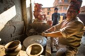 BHAKTAOUR, NEPAL - DEC 7: Unidentified Nepalese man working in the his pottery workshop, Dec 7, 2013