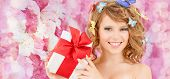 health, holidays and beauty concept - happy teenage girl with butterflies in hair showing gift box