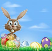 image of ester  - Easter bunny rabbit in a field with a basket of chocolate Easter eggs with copyspace in the sky - JPG