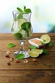 Ingredients for lemonade in glass, on wooden table, on nature background