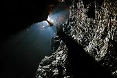foto of cave  - Spelunker abseiling in a cave on a rope - JPG