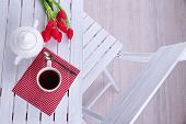 Composition with cup of hot drink, candle and flowers on wooden table background