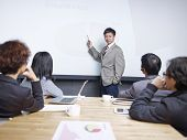 stock photo of conduction  - young man conducting presentation in front of small group of people - JPG