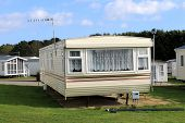 stock photo of trailer park  - Scenic view of trailer on caravan park in summer with cloudscape background - JPG