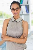 Attractive woman smiling at camera with arms crossed in creative office