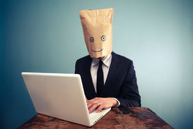 stock photo of incognito  - Businessman With Bag Over Head Working On Computer - JPG