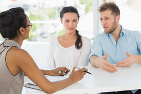stock photo of therapist  - Therapist speaking with couple sitting at desk in therapists office - JPG