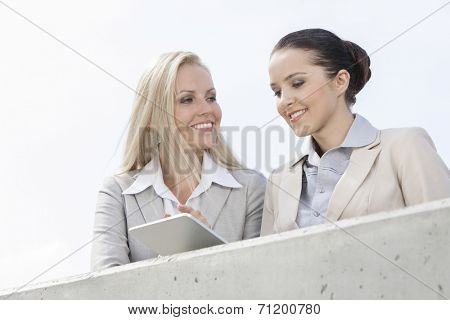 Low angle view of smiling businesswomen using digital tablet while standing on terrace against sky