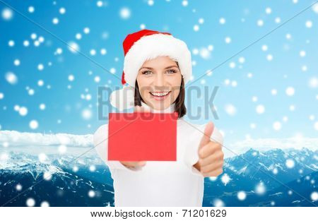 christmas, holdays, people, advertisement and sale concept - happy woman in santa helper hat with blank red card showing thumbs up gesture over snowy mountains background