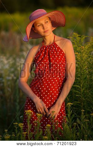 Woman In A Hat Among Wildflowers At Sunset